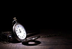Vintage pocket watch on wooden surface on black background with free space for text